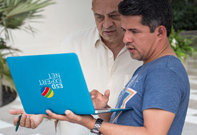 two people are looking at a laptop